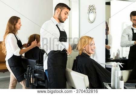 Male Hairstylist Is Making A Haircut For A Happy Woman In A Barbershop. Focus On Client
