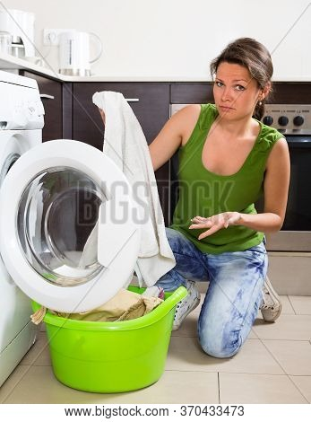 Sad Girl In Jeans Doing Laundry With Washing Machine At Home Kitchen