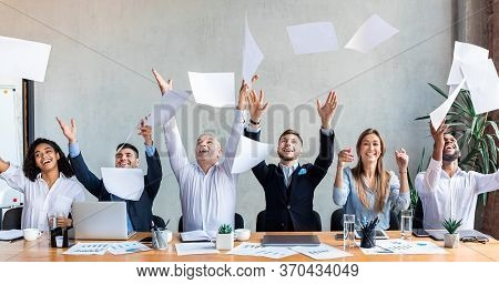 Celebrating Business Success. Joyful Business People Throwing Papers Sitting At One Desk In Modern O