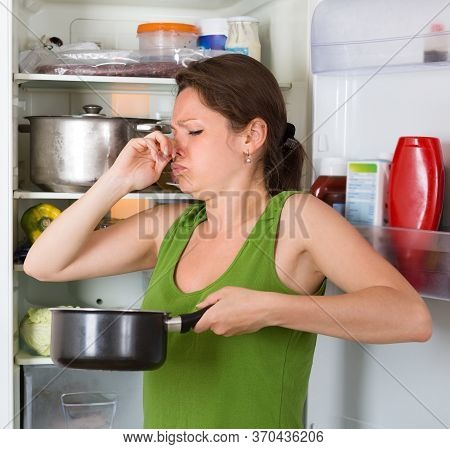 Young Woman Holding Foul Food Near Refrigerator At Home.