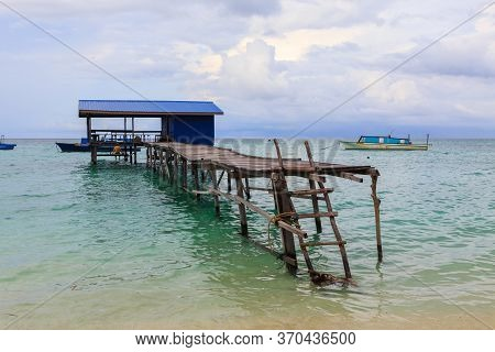Beautiful Scenery Landscape View Of Long Wooden Jetty And White Sand Beach With Blue Sky Ocean And G