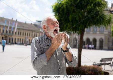 Old man coughs and sneezes into a handkerchief on street, outdoor, hot summer, allergies and illness concept