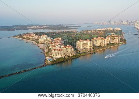 Aerial View Of Fisher Island And Government Cut With City Of Miami Skyline And Port Miami In Backgro