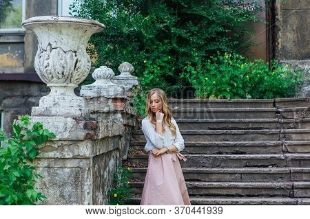Portrait Of A Girl Standing Next To An Old Building With A Decorative Antique Vase And Stairs