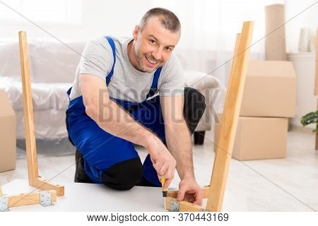 Happy Repairman Assembling Furniture Installing Table After Transportation In New Home, Smiling To C