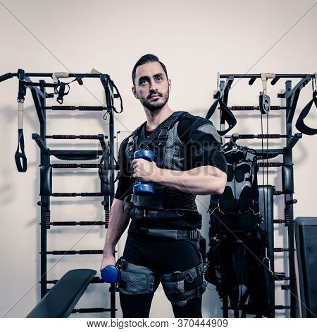Fit Man Having Electro Muscular Stimulation And Training With Dumbbells In Modern Gym