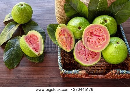Closeup On Red Guava Sliced With Green Leaf On Rustic Wooden Background