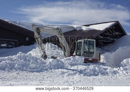 Snow Removal Equipment Stands In A Snowdrift Of Snow. A Machine For Cleaning The Area From Heavy Sno