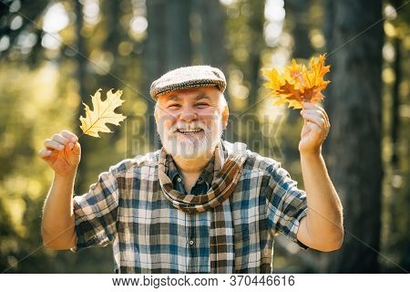 Happy Senior Man. Grandfather Relaxing In Autumn Park. Senior Man Strolling In A Park In Autumn. Map