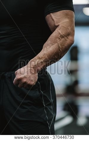 Testosterone Concept Of Body Physique Part Of Strong Male In Black Sportswear Showing Strong Arms Wi