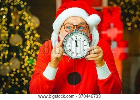 Santa Claus - Bearded Funny Senior. Photo Of Santa Pointing At Clock Showing Five Minutes To Midnigh