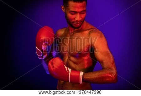 Muscular Boxer In Boxing Gloves Posing On Blue Studio Background With Red Lights. Professional Kickb