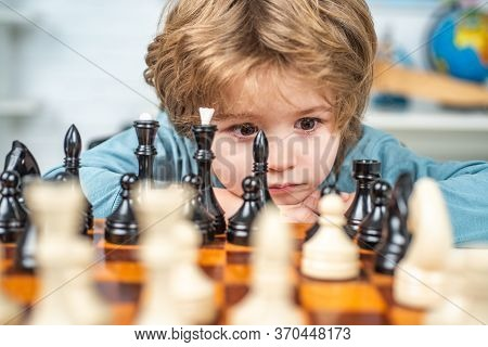 Little Boy Playing Chess. Boy Kid Playing Chess At Home. Clever Concentrated And Thinking Child Whil