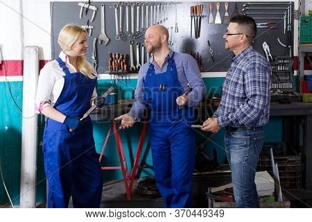 Two Smiling Workers And Adult Superviser At Auto Repair Shop. Focus On The Man