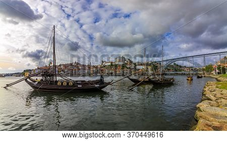 Porto, Portugal - May 31, 2018: Traditional Old Rabelo Boats With Barrels Of Port Wine Docked On Dou