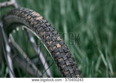 Close Up Of Checkerboard Tire Bike Wheel Covered With Dirt. Mountain Bike Wheels Covered With Clay.