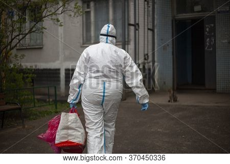 A Doctor In A Protective Suit Goes To The House. Virologist Arrived To Undergo A Coronavarius Test.