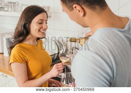 Focus Of Bi-racial Man Holding Bottle Of Wine Near Glasses And Smiling Girlfriend