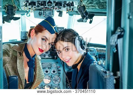 Two Women Pilots Sitting In Cabin Of Modern Aircraft. Smiling Stewardess In The Aircraft. Portrait O