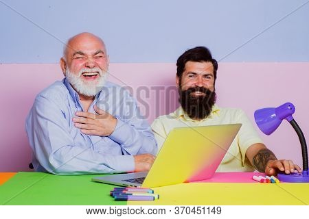 Two Businessmen Laughing Out Loud At Workplace. Two Office Workers Laughing Watching Funny Content A