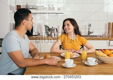 Woman Looking At Bi-racial Boyfriend Near Tasty Breakfast On Table