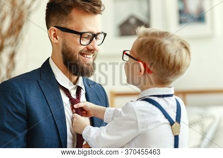 Happy Family On Father's Day. Happy Son Helps Dad Tie A Necktie At Home