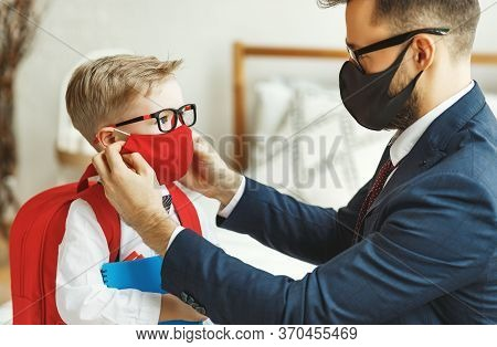 Businessman Father Accompanies His Little Son To School Putting On A Mask To Protect And Prevent Cor