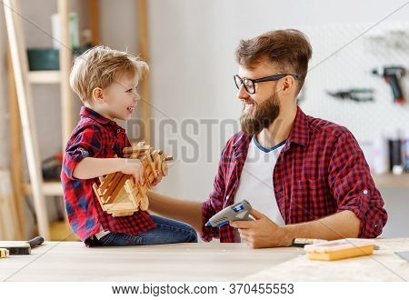 Happy Little Boy Helping Father While Creating Wooden Toy Car At Workbench And Enjoying Time Togethe