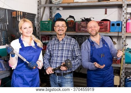 Portrait Of Two Smiling Troubleshooters And Superviser At Auto Repair Shop