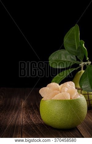 Fresh Pomelo, Pummelo, Grapefruit, Shaddock On Wooden Table Over Black Background, Close Up, Copy Sp