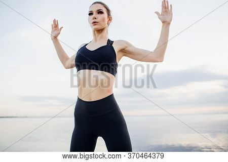 Young Woman In Black Sportswear Stretching Hands By The River. Fitness Girl With Hands Raised Above