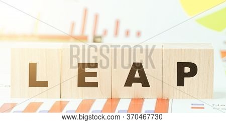 Word Leap Made With Black Letters On Wooden Cubes On Table With Different Color Graphs And Diagram A