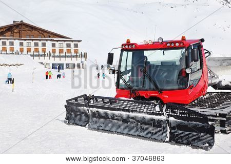Red machine for skiing slope preparations in Austrian Alps, building and tourists.
