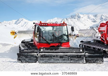 Big red machines for skiing slope preparations in Austrian Alps at day.