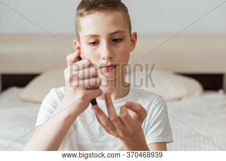 Teen Boy Takes A Blood Sample For Diabetes With Lancet Pen. Health, Medicine And Diabetic Concept
