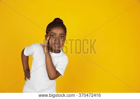 Whispering A Secret. Little African-american Girls Portrait On Yellow Studio Background. Cheerful, B