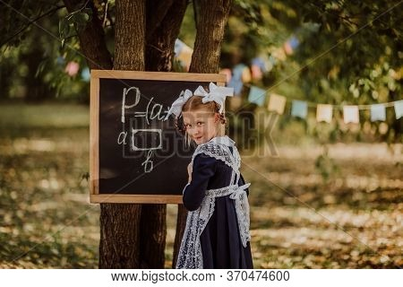 Young Girl In School Uniform With White Bows Writing On A Board In A Park. Back To School.copy Space