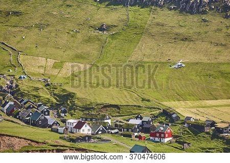 Helicopter Flying Over Mykines Village In Faroe Islands. Denmark