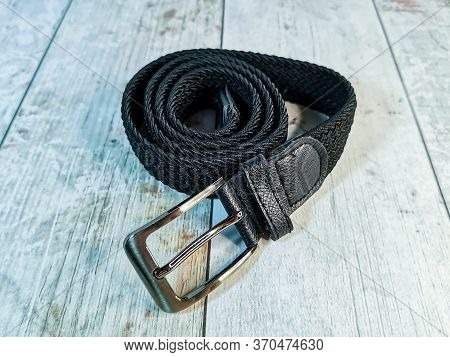 Black Wicker Trouser Belt With A Silver Buckle On A Wooden Tabletop Background. Rolled Up Trouser Be