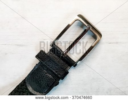 Close-up Of A Silver Buckle From A Trouser Belt On A Wooden Tabletop Background. Accessories And Ele