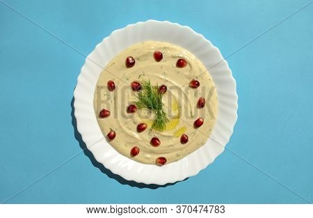 Famous Traditional Arabic, Eastern And Israel Cuisine - Tahini Dip With Pomegranate On Blue Backgrou