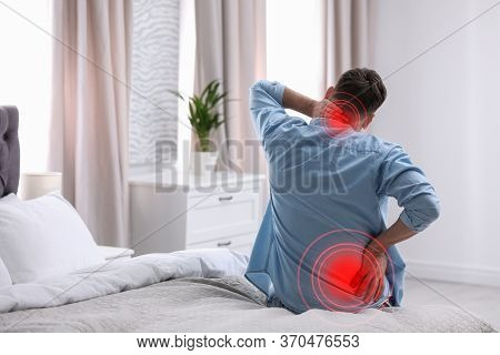 Man Suffering From Back Pain After Sleeping On Uncomfortable Mattress At Home
