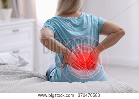 Senior Woman Suffering From Back Pain After Sleeping On Uncomfortable Mattress At Home, Closeup
