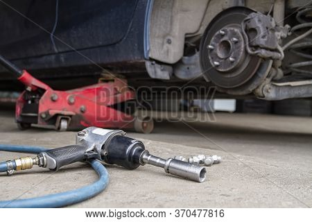 Pneumatic Wrench Tool On The Asphalt And A Car Jack For Lift Up The Body And Changing The Tire. Car