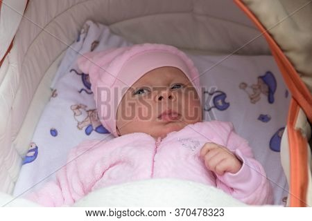 Baby In A Stroller In A Pink Jacket, Newborn Baby Girl In A Fluffy Pink Jacket Lies In A Stroller