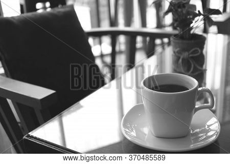 Monotone Image Of A Cup Of Coffee On A Table With Empty Chair