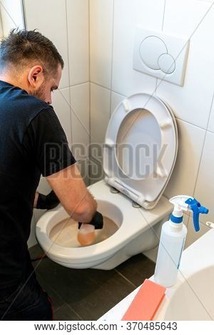 Professional Cleaner Cleans A Ceramic Toilet Very Thoroughly In A Modern Bathroom