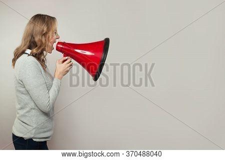 Real Woman Screaming With Loudspeaker Megaphone. Girl Holding Red Bullhorn