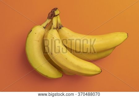 Bunch Of Ripe Bananas On A Bright Orange Background. Spotted Overripe Fruits. View From Above. Abstr