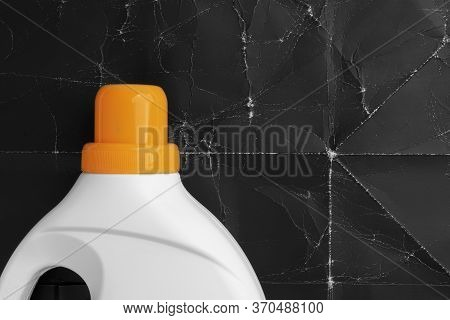 Laundry Detergent In A Plastic White Container With A Bright Orange Screw Cap On A Background Of Old